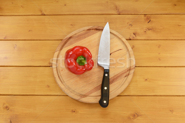 Red pepper with a knife on a chopping board Stock photo © sarahdoow