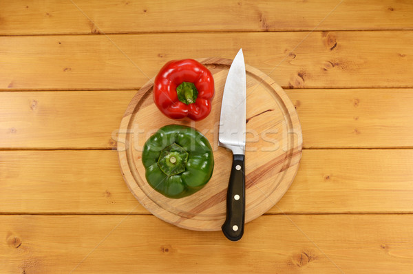 Red and green peppers with a knife on a chopping board  Stock photo © sarahdoow
