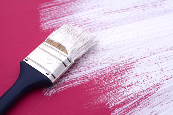 Dirty paintbrush with white paint on half-painted board Stock photo © sarahdoow