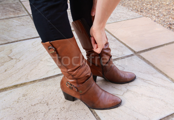 Young woman zipping up her fashionable leather boots Stock photo © sarahdoow