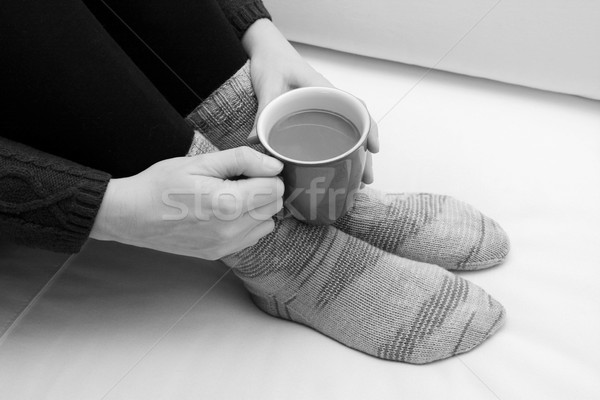 Woman holding a hot drink, wearing warm knitted socks Stock photo © sarahdoow