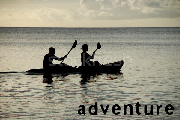 Kayakers silhouetted on the ocean, ADVENTURE as concept text Stock photo © sarahdoow