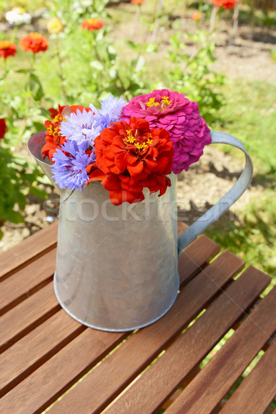 Pitcher filled with fresh flowers on a garden table Stock photo © sarahdoow