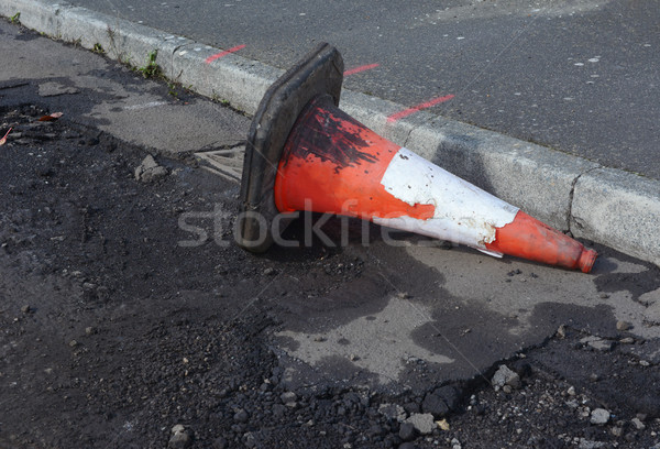 Damaged traffic cone in gutter, road undergoing repairs Stock photo © sarahdoow