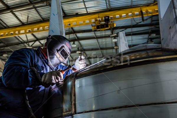 Man welding with reflection of sparks on visor. Hard job.  Stock photo © sarymsakov