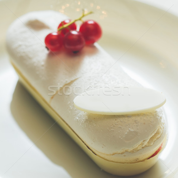 Single eclair with space for text on white plate. Stock photo © sarymsakov