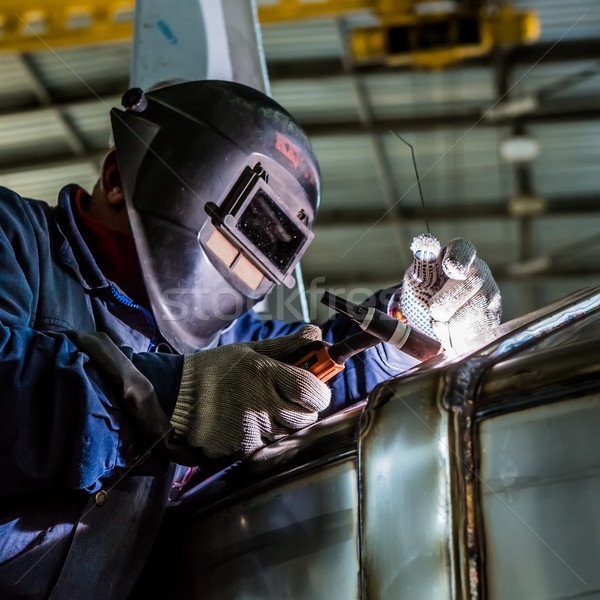 Man welding with reflection of sparks on visor. Hard job.  Stock photo © sarymsakov