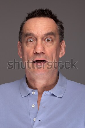 Man Pulling Face Sticking Out Tongue on Grey Background Stock photo © scheriton
