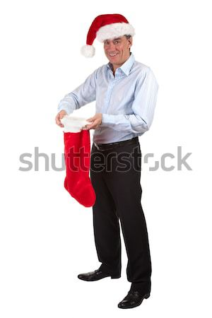 Happy Smiling Business Man in Santa Hat pleased with contents of Christmas Stocking Stock photo © scheriton