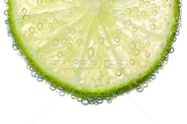 Lime Slice in Clear Fizzy Water Bubble Background Stock photo © scheriton