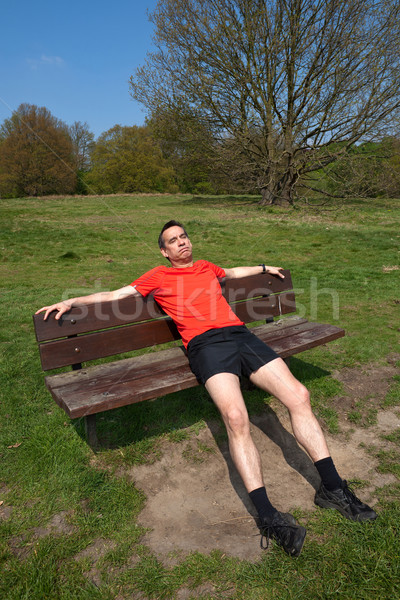 Tired Man Exercising Resting on Sunny Park Bench Stock photo © scheriton