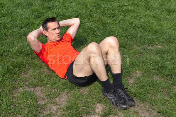 Man Exercising doing Situps on the Grass Stock photo © scheriton
