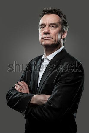 Stern Imposing Business Man with Arms Folded on Grey Background Stock photo © scheriton