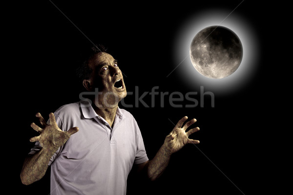 Scary Man Turning into Werewolf or Beast Under a Cloudy Full Moon Stock photo © scheriton