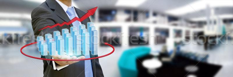 Stock photo: Businessman in his office holding chart