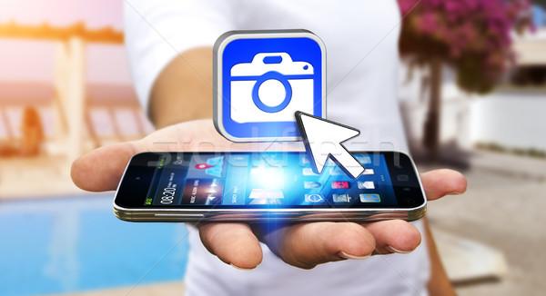 молодым человеком современных камеры применение мобильного телефона стороны Сток-фото © sdecoret