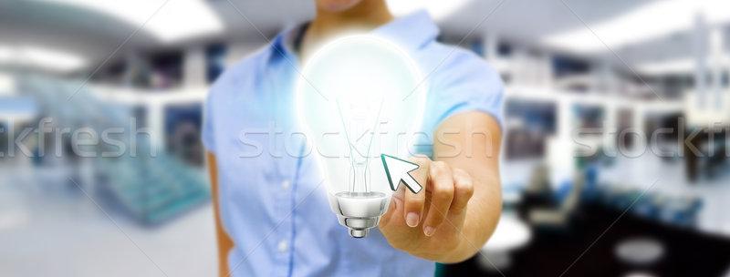 Businesswoman holding lightbulb Stock photo © sdecoret