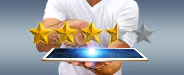 Stock photo: Businessman rating stars with his tablet