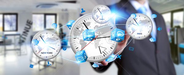 Businessman connecting time of the world in his hand Stock photo © sdecoret