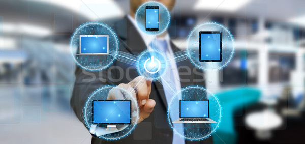 Businessman connecting tech device with his finger Stock photo © sdecoret