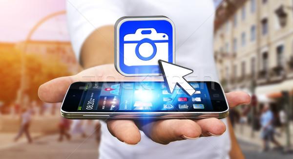 Fiatalember modern kamera alkalmazás mobiltelefon kéz Stock fotó © sdecoret