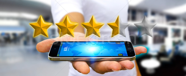 Businessman rating stars with his mobile phone Stock photo © sdecoret