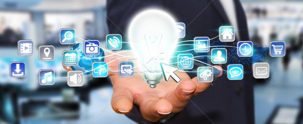Businessman holding lightbulb with digital icons Stock photo © sdecoret