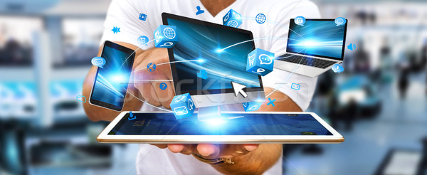 Businessman connecting tech device with his tablet Stock photo © sdecoret