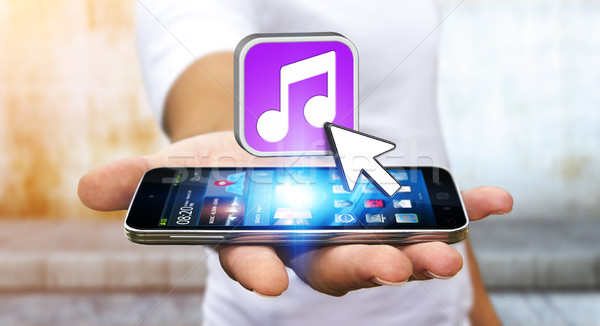 Young man using modern mobile phone to listen music Stock photo © sdecoret