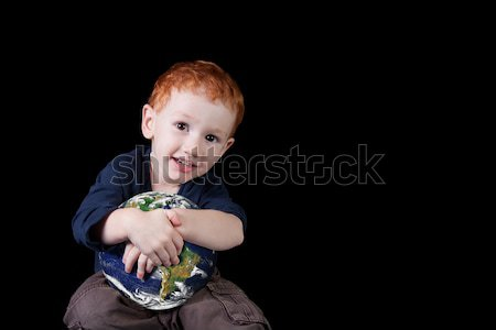 Boy holding world and smiling. Stock photo © sdenness