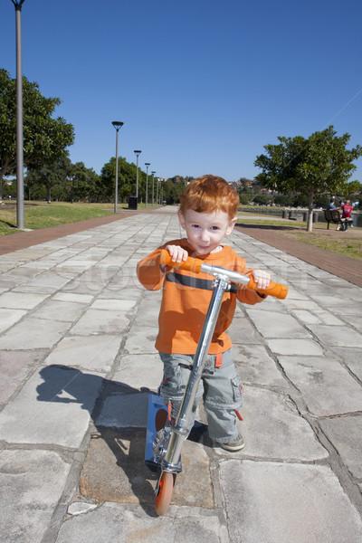 Kisgyerek moped park fiatal srác út égbolt Stock fotó © sdenness