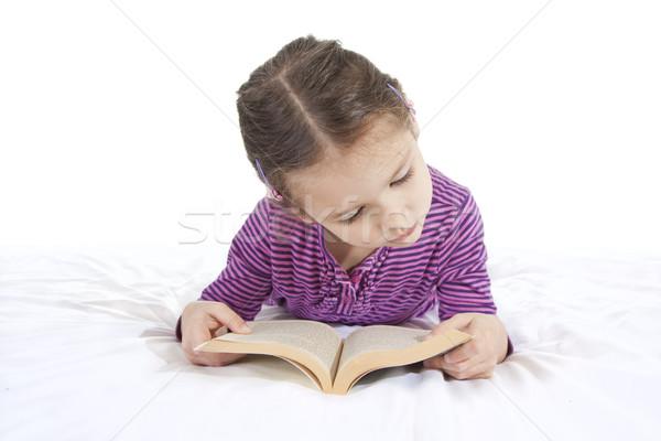 Fiatal lány olvas fekszik könyv fehér lány Stock fotó © sdenness