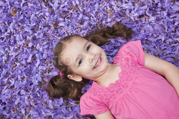 Young girl lying among fallen flowers Stock photo © sdenness