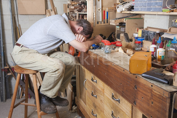 Stock photo: Head on arms on workbench
