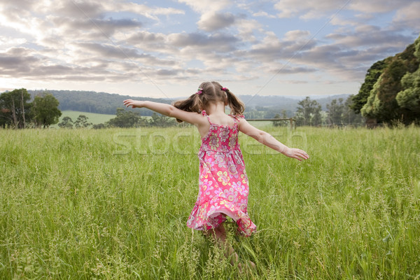 Girl running through long grass Stock photo © sdenness
