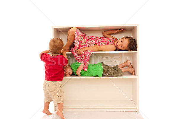 Three young kids playing on bookshelves Stock photo © sdenness