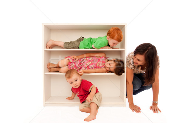 Kids playing hide and seek with mum on bookshelf Stock photo © sdenness
