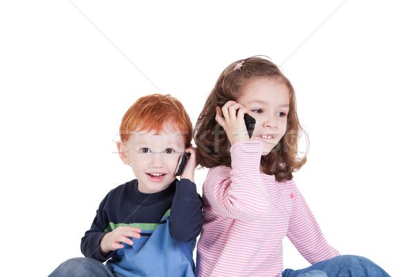 Szczęśliwy dzieci telefony komórkowe dwa mówić odizolowany Zdjęcia stock © sdenness
