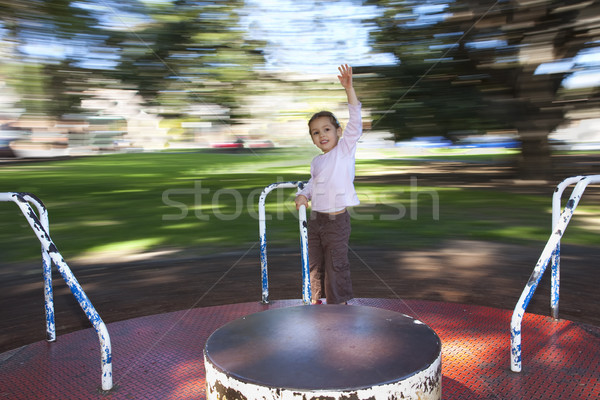 Girl on moving roundabout Stock photo © sdenness