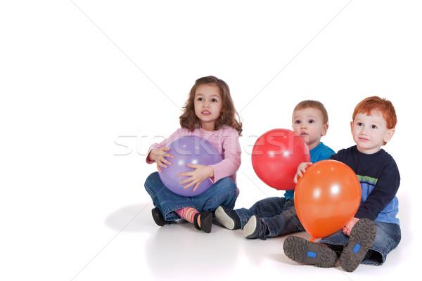 Trzy dzieci balony strony posiedzenia w dół Zdjęcia stock © sdenness