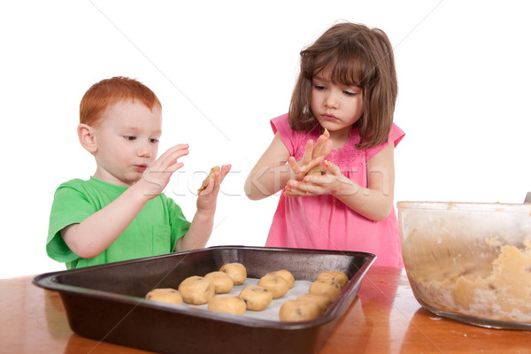 Kids rolling out chocolate chip cookies for baking Stock photo © sdenness
