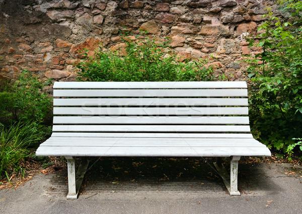 Wooden bench near a stone wall Stock photo © Serg64