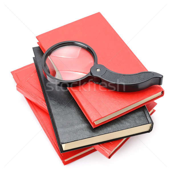 Large magnifier on book stack isolated on white. Stock photo © serg64