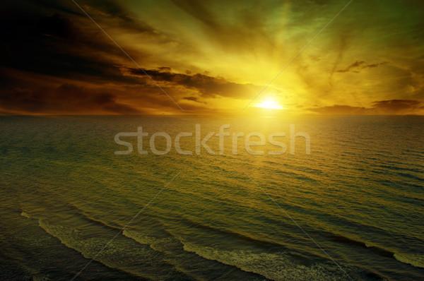 Hajnal tenger drámai felhők alkonyat tengerpart Stock fotó © serg64