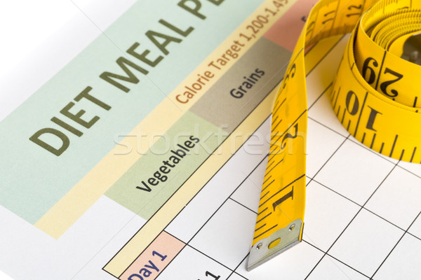 Dieting weight loss concept - measurement tape on meal planning  Stock photo © ShawnHempel