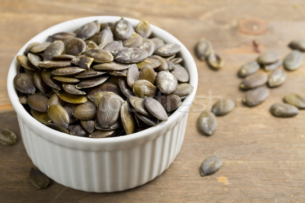 Unshelled pumpkin seeds in white bowl Stock photo © ShawnHempel
