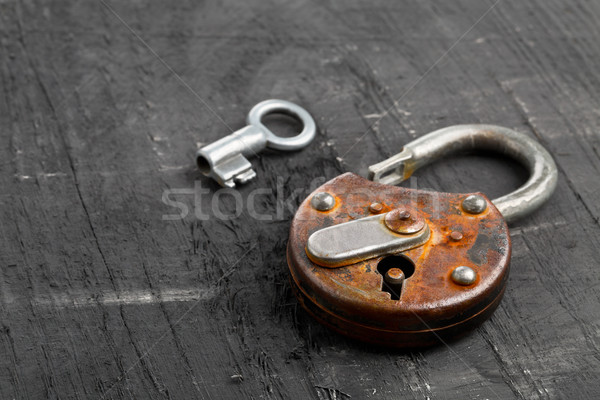 Open antique padlock with key on black Stock photo © ShawnHempel