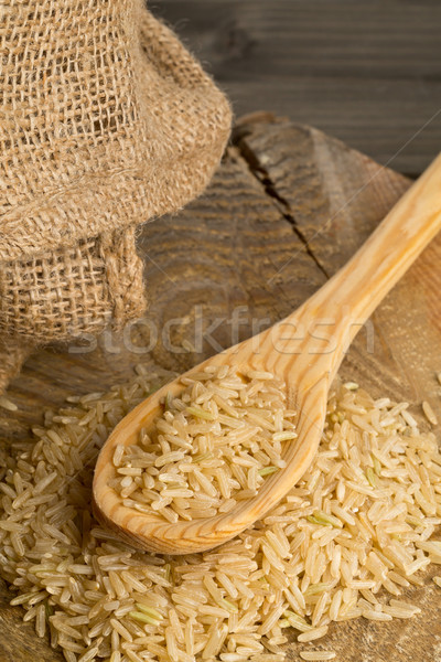 Natural brown uncooked rice on wooden spoon Stock photo © ShawnHempel