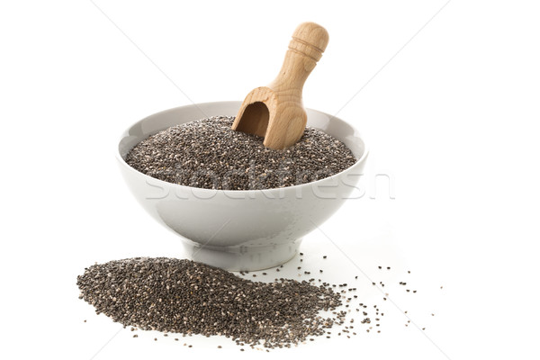 Raw, unprocessed, dried black chia seeds in white bowl with wood Stock photo © ShawnHempel