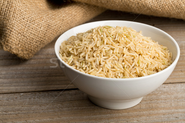 Natural brown uncooked rice in white bowl Stock photo © ShawnHempel